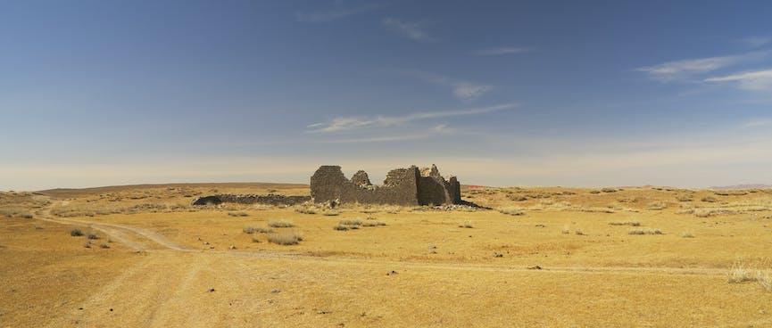 The empty desert landscape around the derelict stone walls.