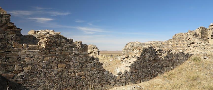 A v-shaped hole in a tall stone wall.