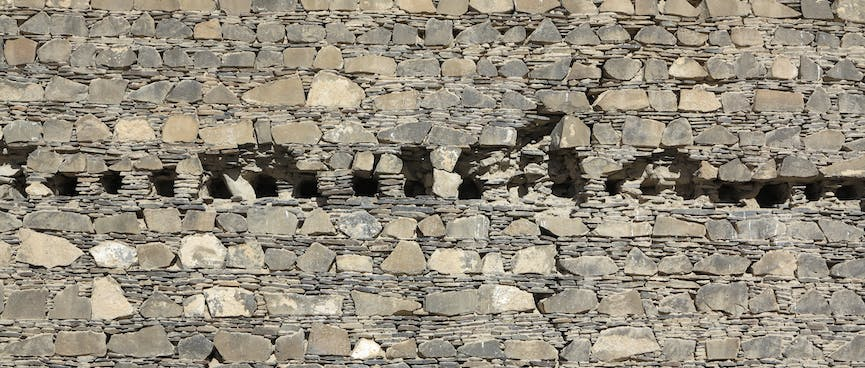 A row of holes in the centre of a stone wall.