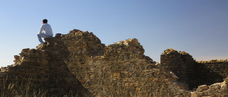 A man sits on top of derelict stone walls.