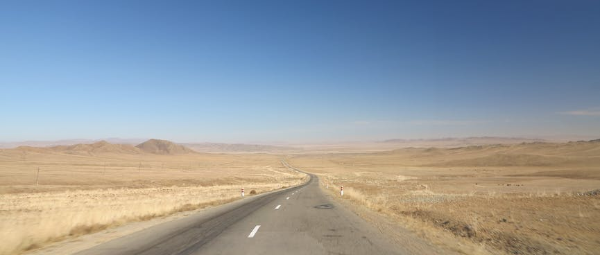 A grey two lane highway stretches through a light brown landscape.