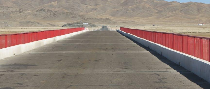 Red metal rails run along the sides of an asphalt road bridge.