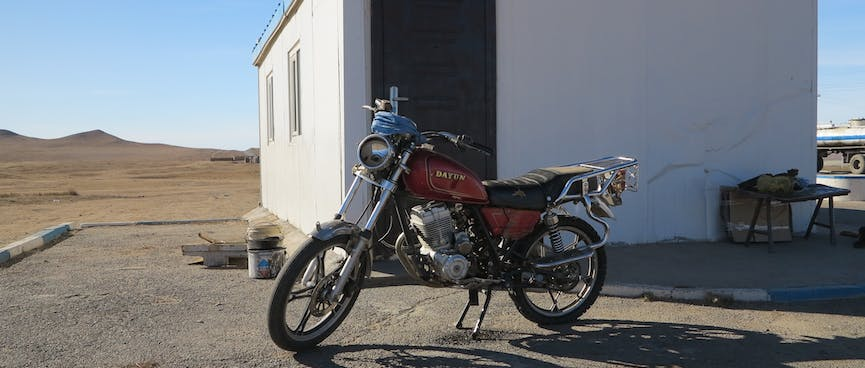 A red Dayun motorcycle parked outside a square white building with blue trim.