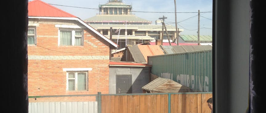 The view out of the window includes a tired two-storey house, half a shipping container and some low key construction.