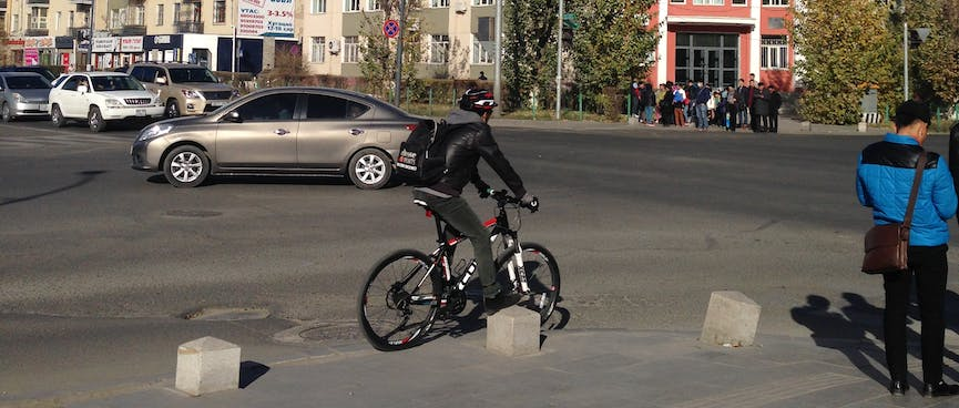 A man's bike, helmet, bag and jacket share a black, white and red colour scheme.