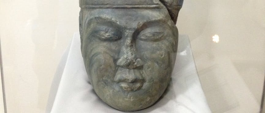 Carved stone head with closed eyes wearing a tall ceremonial headdress.