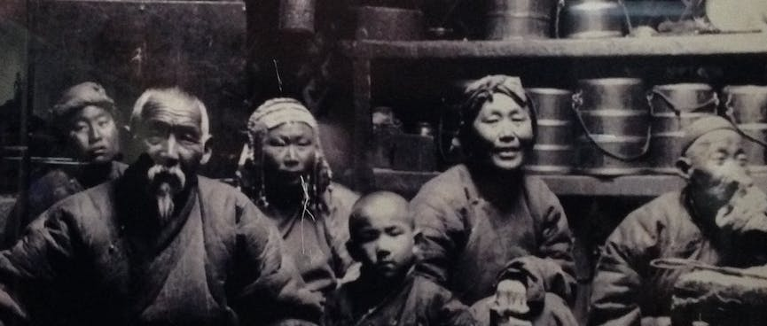 A black and white photo of a Mongolian family seated on the floor with cooking utensils behind them.