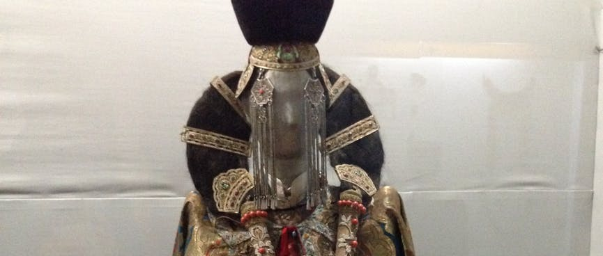 A mannequin in gold and red ceremonial robes has her hair tied in a loop.
