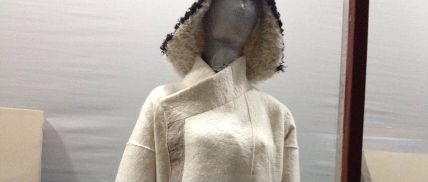 A mannequin wears a furry hat and a white cloak with light brown belt and trim.