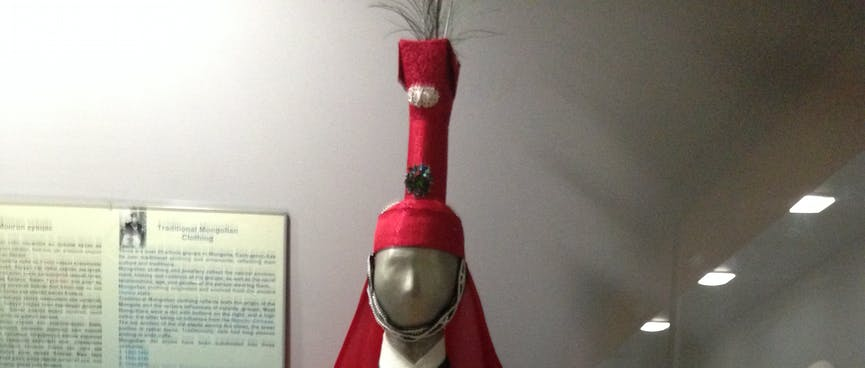A mannequin wears a ceremonial cloak and a matching hat with a tall narrow extension.