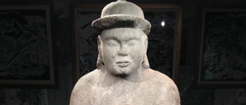 A stone man wears a bowler hat and holds a cup in one hand.