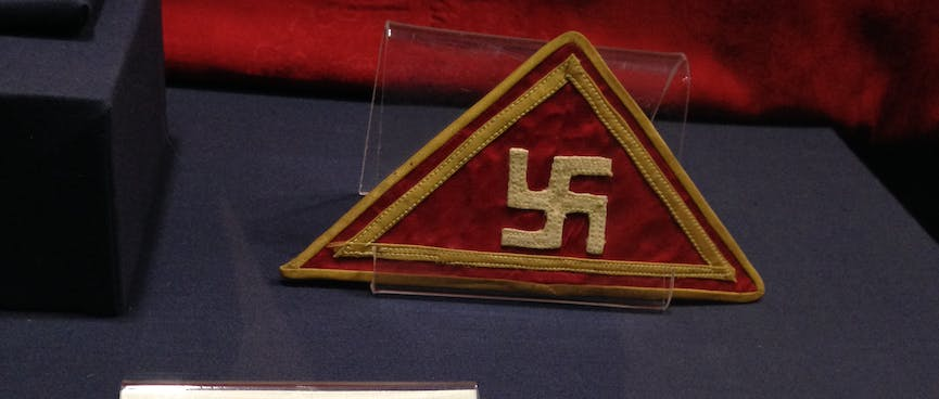 A sewn triangle badge with a gold swastika and border.