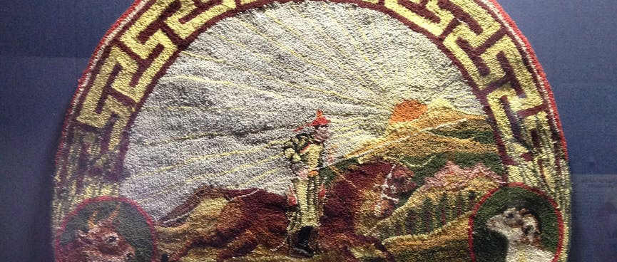 A felt badge showing a rider on a galloping brown horse, under a bright sun. Four other animals are featured on the border of the badge.