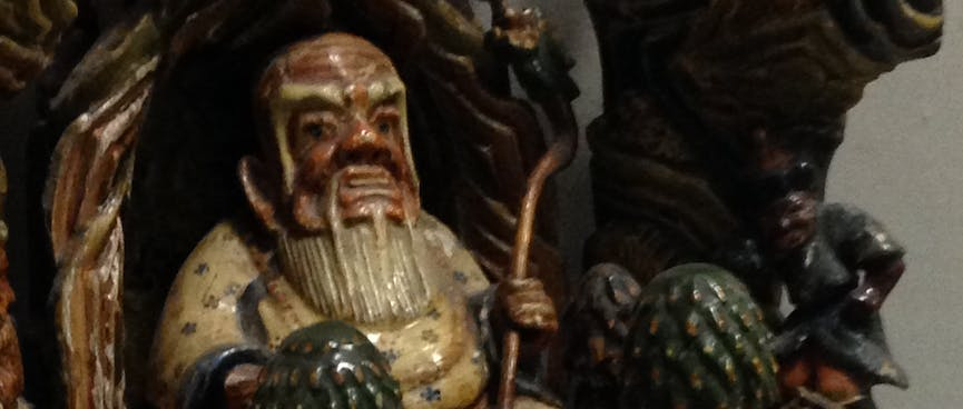 A shiny painted wooden statue showing a fat man with a white beard sitting in a doorway.