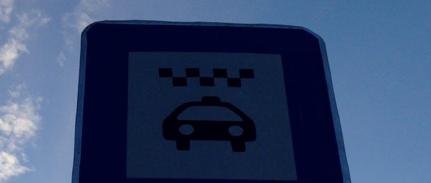 A rectangular sign displays a taxi icon.