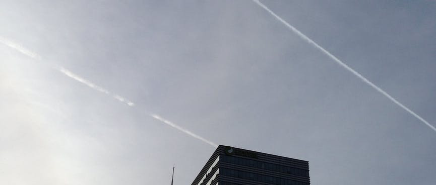 Twin vapour trails in the blue skies above an office block.
