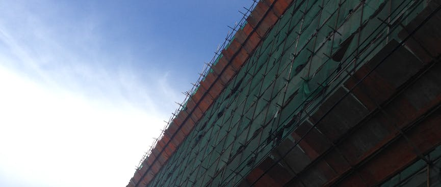 The side of a building is wrapped in green and red mesh.